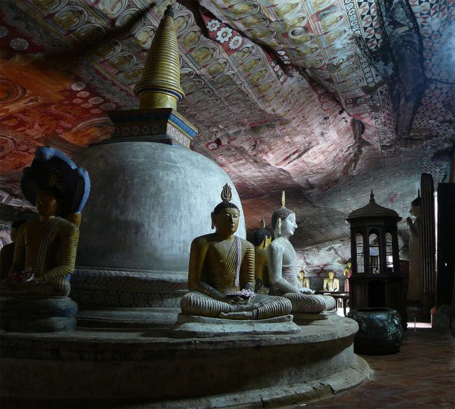 Statues of the Buddha in the Cave of the Great Kings. The intricate murals covering the stone walls depict scenes from the Buddha's life. Image courtesy: wikimedia.org