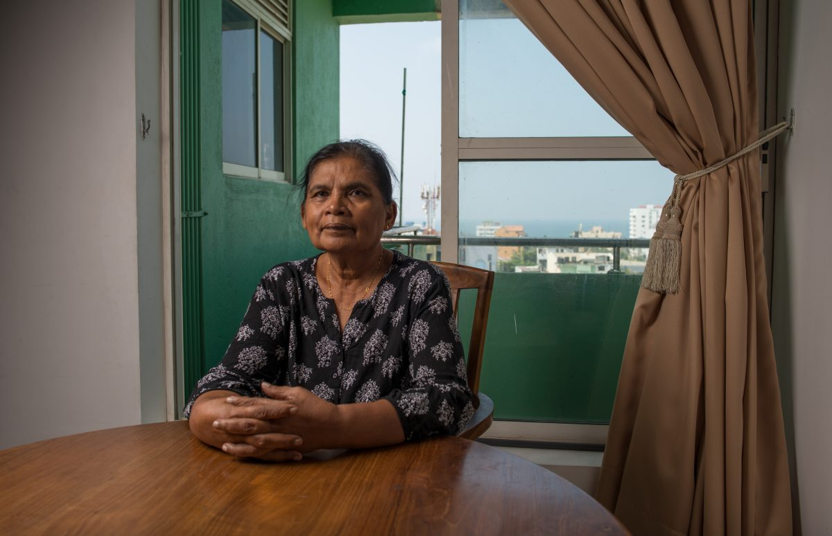 Kumala sits at the table in her living room, with an unspoiled view of the sea behind her. Image credit: Roar.lk/Christian Hutter