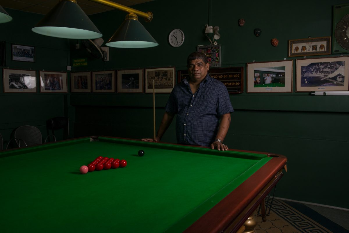 Noor stands at the billiard table, on the second floor of the Cue Club in Slave Island. Playing billiards or snooker has been a tradition in his family for more than a hundred years. Image credit: Roar.lk/Christian Hutter