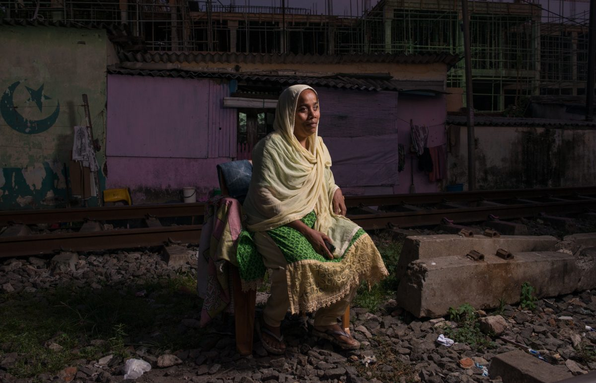 Nona sits on a plastic chair, in between the railway tracks that border her house. Image credit: Roar.lk/Christian Hutter