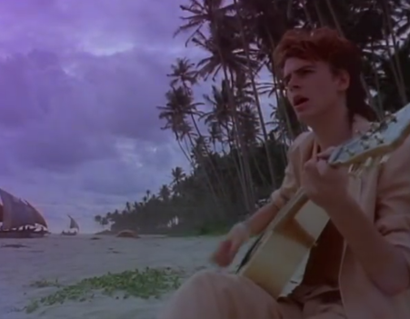 Bassist John Taylor strumming on acoustic by the beach. Credit: YouTube.