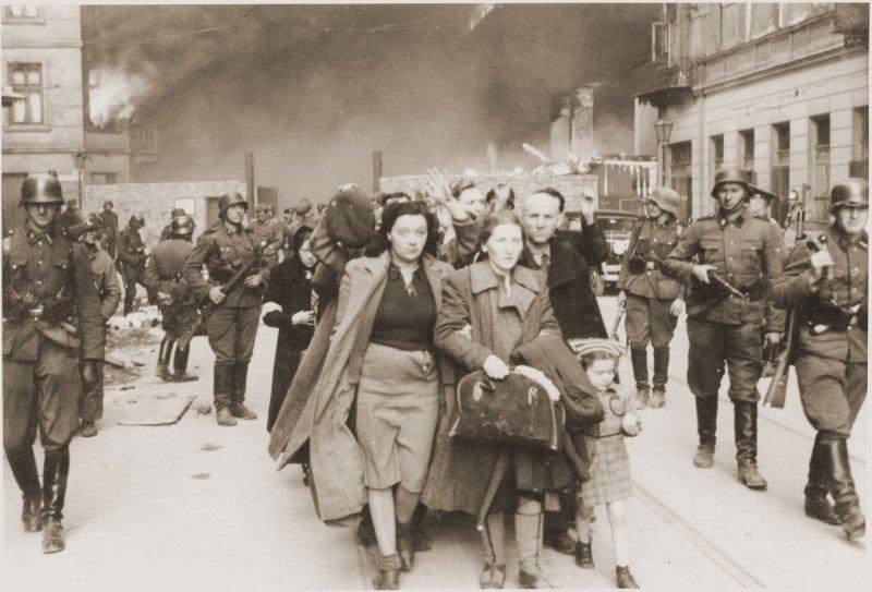 https://assets.roar.media/assets/M9hJw5cwUGI4lu0Z_family-marching-Jews-head-column-way-Warsaw-1943.jpg